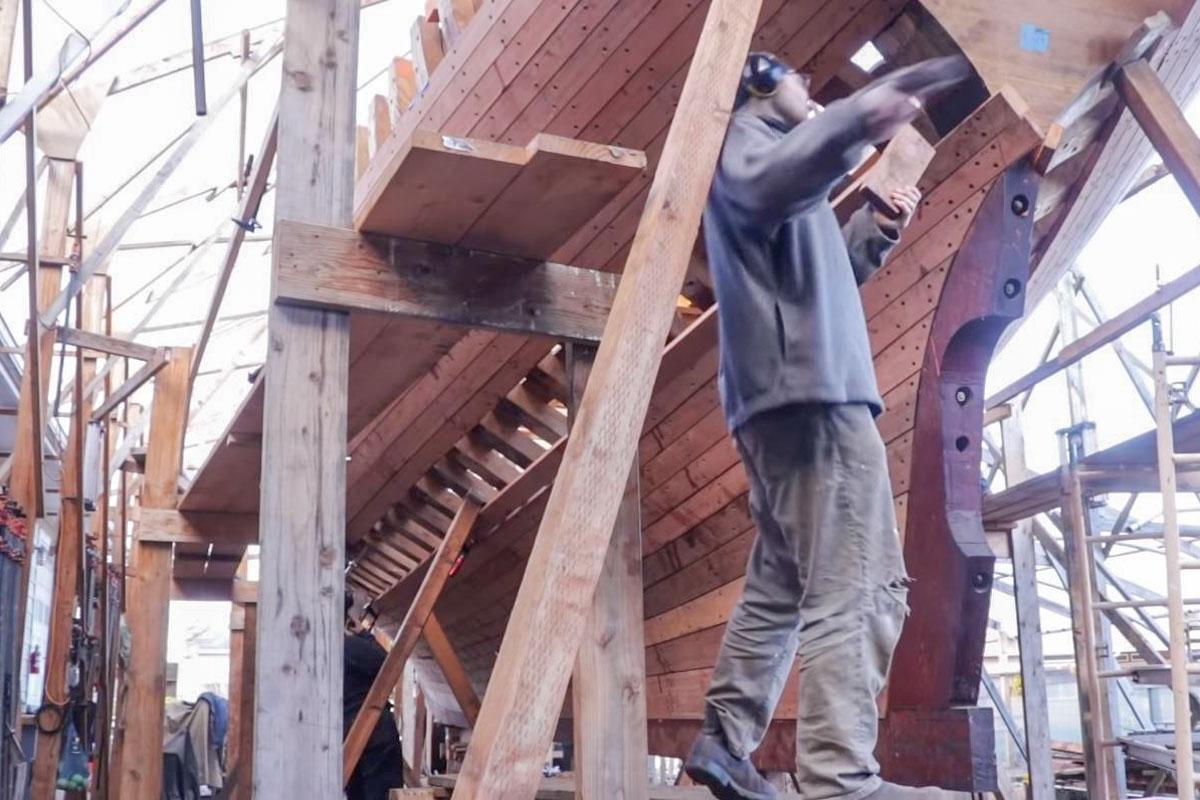 Rowan haut mit einem Hammer auf die Planke
