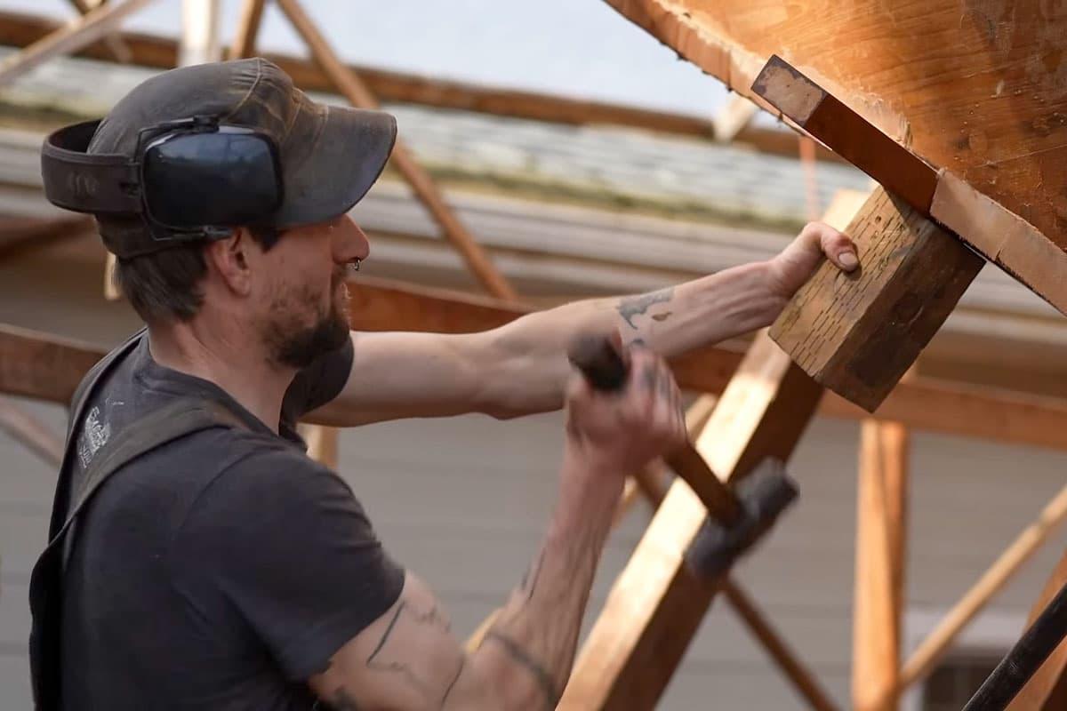Mit einem Hammer wird an der Planke gearbeitet