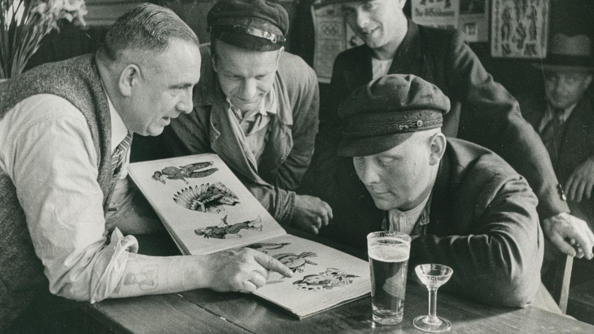 Christian Warlich erklärt potenziellen Kunden anhand seines Musterbuchs Preise und Aufwand der Tattoos © Warlich